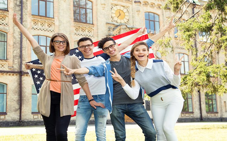 Group Of Students Holding Flag Of Usa On The University Campus.